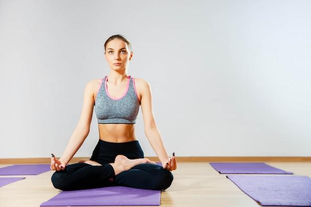 Młoda kobieta siedzi na podłodze w pozycji lotosu podczas medytacji