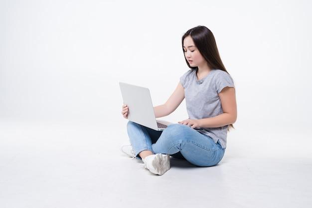 Młoda kobieta siedzi na podłodze z laptopem na białym tle na białej ścianie