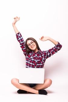 Młoda kobieta siedzi na podłodze z laptopem na białym tle