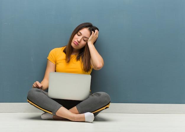 Młoda kobieta siedzi na podłodze z laptopem zmęczony i bardzo śpiący