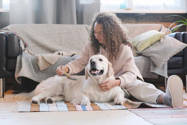 Młoda kobieta siedzi na podłodze z psem i czesanie jego futra w salonie w domu