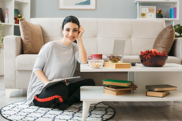 Młoda kobieta siedzi na podłodze za stolikiem kawowym w salonie