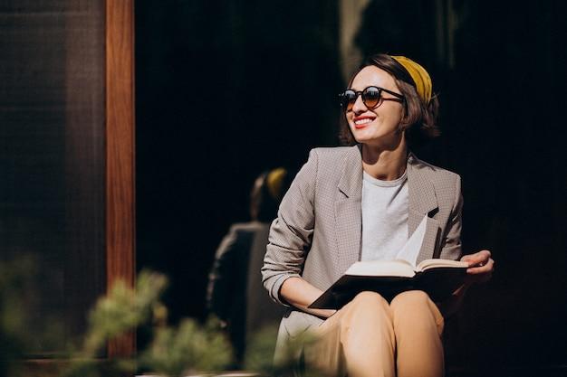 Młoda kobieta siedzi na podwórku i czytanie książki