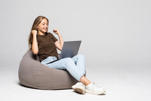 Młoda kobieta siedzi na pufff z laptopem z gestem wygranej na białym tle na białej ścianie