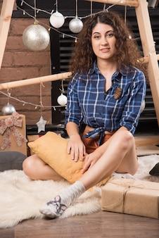 Młoda kobieta siedzi na puszystym dywanie z dekoracjami świątecznymi