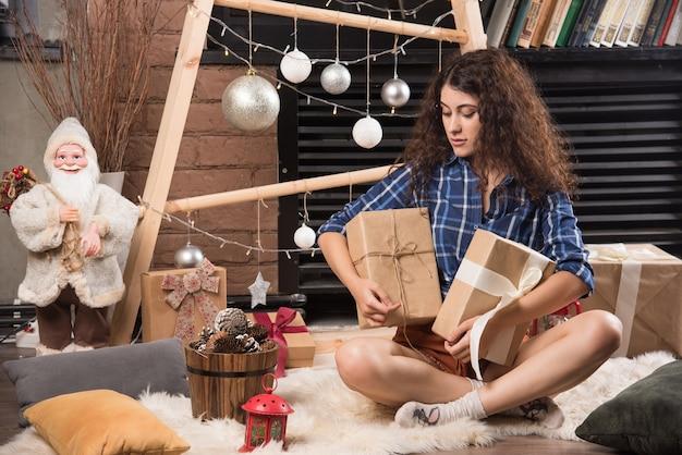 Młoda kobieta siedzi na puszystym dywanie z pudełkami świątecznych prezentów