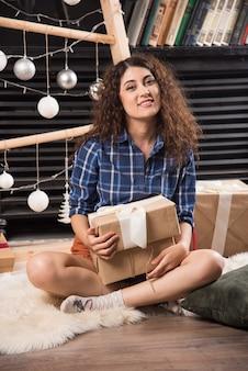 Młoda kobieta siedzi na puszystym dywanie z pudełkiem świątecznych prezentów