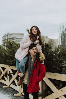 Młoda kobieta siedzi na ramionach mężczyzny