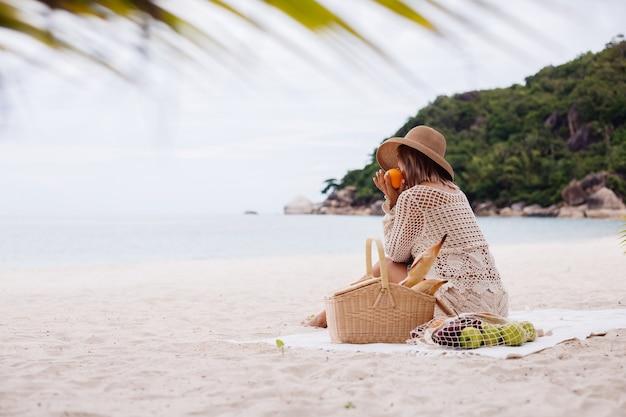 Młoda kobieta siedzi na ręczniku w słomkowym kapeluszu i białej dzianinie z koszem piknikowym