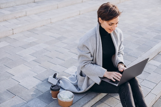 Młoda kobieta siedzi na schodach i pracuje na komputerze