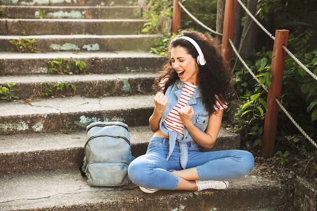Młoda kobieta siedzi na schodach na zewnątrz