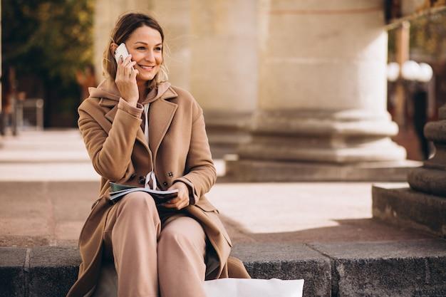 Młoda kobieta siedzi na schodach w mieście i czytania magazynu i rozmawia przez telefon