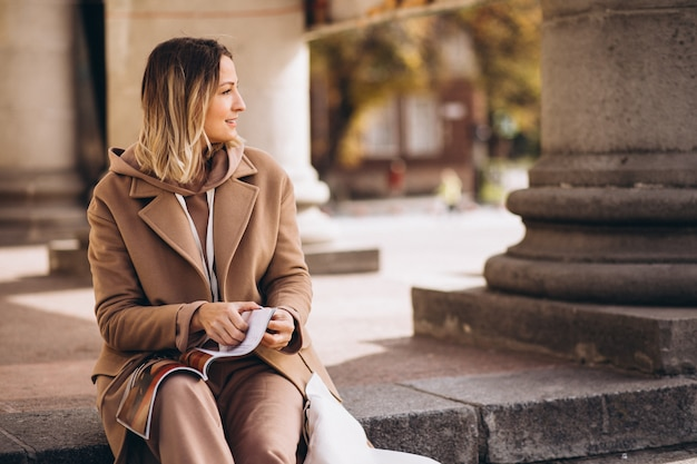 Młoda kobieta siedzi na schodach w mieście i czytania magazynu