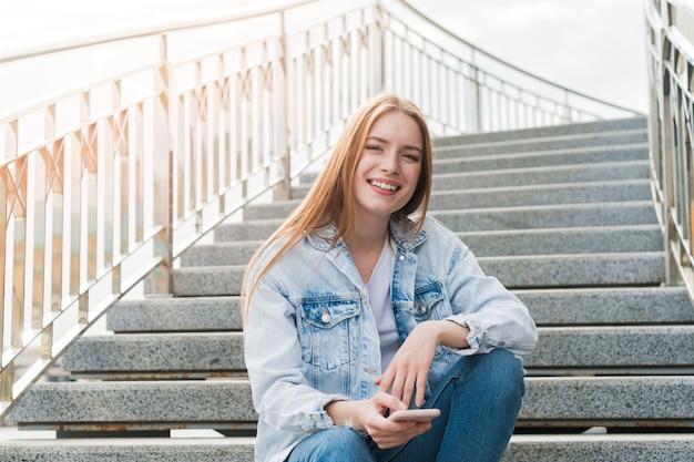 Młoda kobieta siedzi na schody patrząc na kamery z gospodarstwa telefon