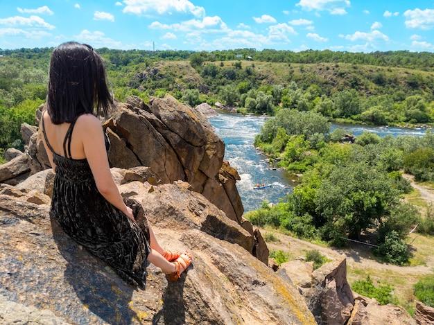 Młoda kobieta siedzi na skale i patrzy na malowniczy krajobraz południowej rzeki bug. park narodowy straży bugu na ukrainie.
