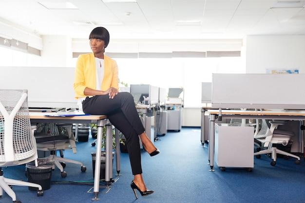 Młoda kobieta siedzi na stole w biurze