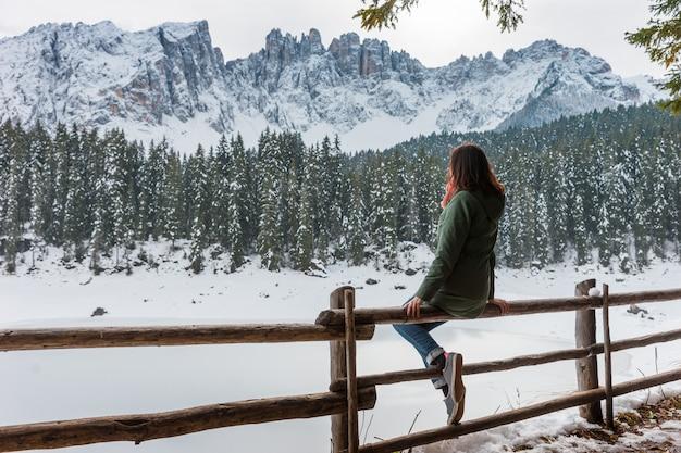 Młoda kobieta siedzi na tle zimowego jeziora i gór. dziewczyna podziwia malowniczy zimowy krajobraz: zaśnieżone jezioro i góry. zimowa góra we włoszech, jezioro carezza