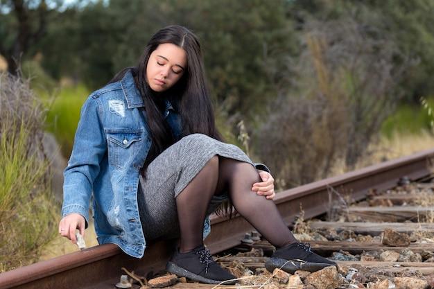Młoda kobieta siedzi na torze pociągu, pisząc z kamienia.