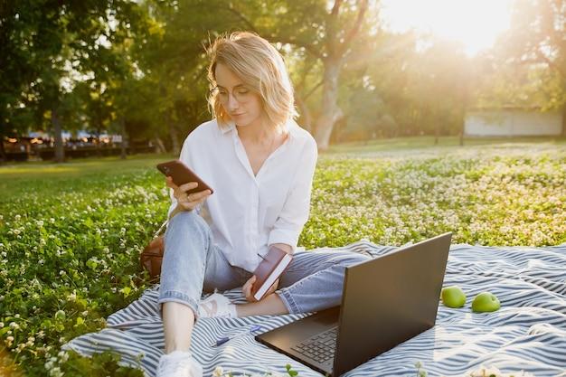 Młoda kobieta siedzi na trawniku w parku używa laptopa i smartfona