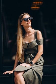 Młoda kobieta siedzi na zewnątrz kawiarni