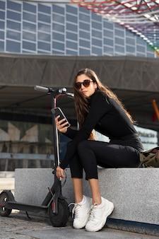 Młoda kobieta siedzi obok skutera