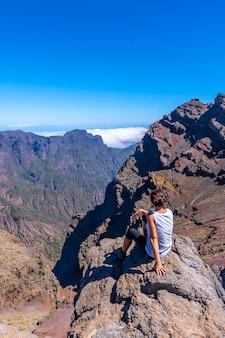 Młoda kobieta siedzi odpoczywając i patrząc na widoki na park narodowy roque de los muchachos na szczycie caldera de taburiente, la palma, wyspy kanaryjskie. hiszpania
