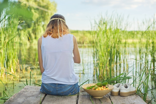 Młoda kobieta siedzi plecami na drewnianym molo