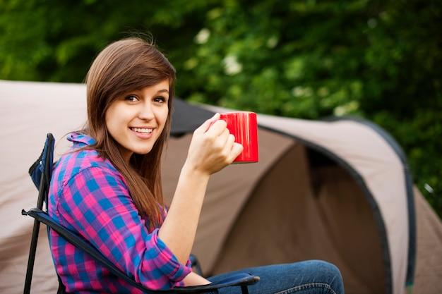 Młoda kobieta siedzi przed namiotem