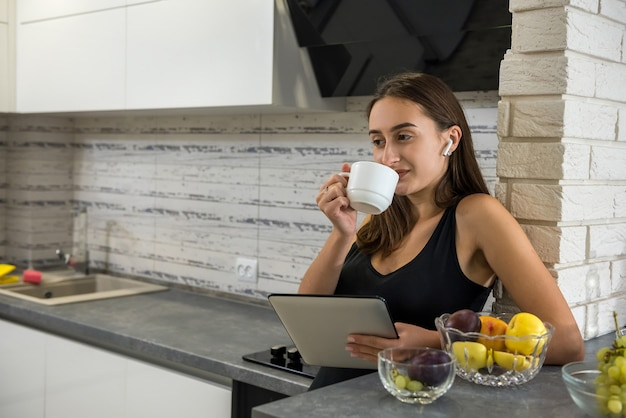 Młoda kobieta siedzi przed otwartym laptopem i picia kawy w swojej kuchni. ciesz się czasem w domu