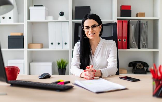 Młoda kobieta siedzi przy biurku komputerowym.