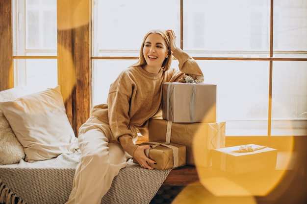 Młoda kobieta siedzi przy oknie z prezentami