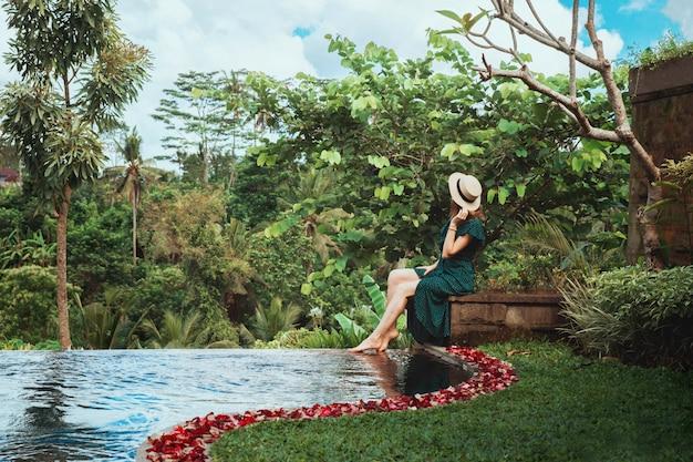 Młoda kobieta siedzi przy otwartym prywatnym basenie z widokiem na tropikalną dżunglę, ubud