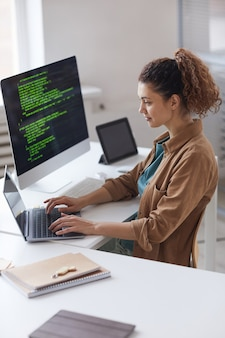 Młoda kobieta siedzi przy stole i koncentrując się na pracy online na laptopie pracującym w serwisie komputerowym