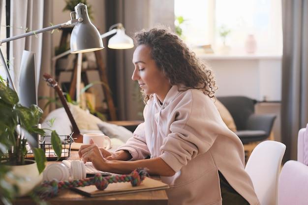 Młoda kobieta siedzi przy stole i pracuje online na komputerze w domu