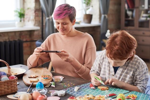 Młoda kobieta siedzi przy stole i robi zdjęcie swojego rzemiosła przez telefon z chłopcem dekorującym ciasteczka w pobliżu
