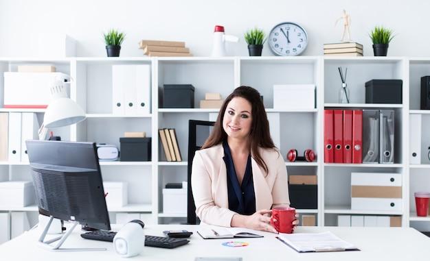 Młoda kobieta siedzi przy stole komputerowym, trzyma czerwony kubek i patrzy prosto.