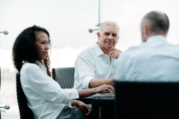 Młoda kobieta siedzi przy stole negocjacyjnym w centrum biznesowym