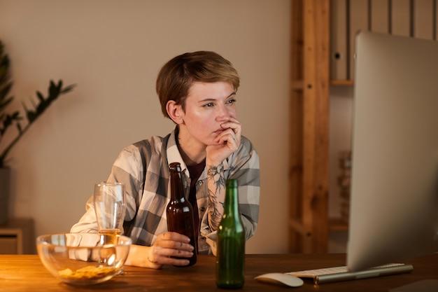 Młoda kobieta siedzi przy stole przed monitorem komputera, oglądając film i pijąc piwo w domu