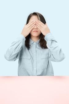 Młoda kobieta siedzi przy stole w studio z zamkniętymi oczami, odizolowane na niebiesko. nie widzę nic