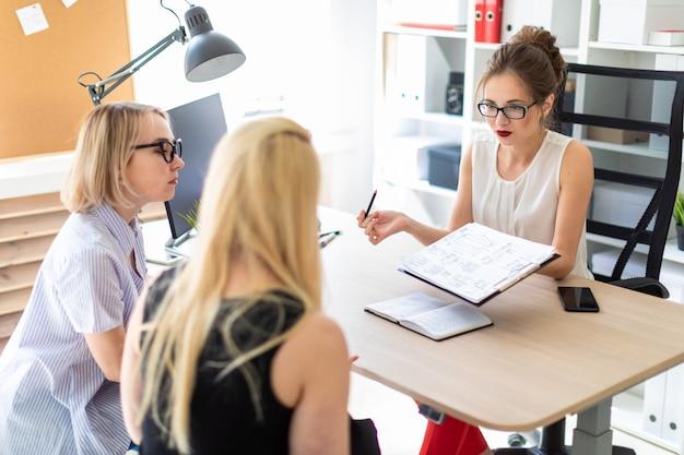 Młoda kobieta siedzi przy stole w swoim biurze i rozmawia z dwoma partnerami.