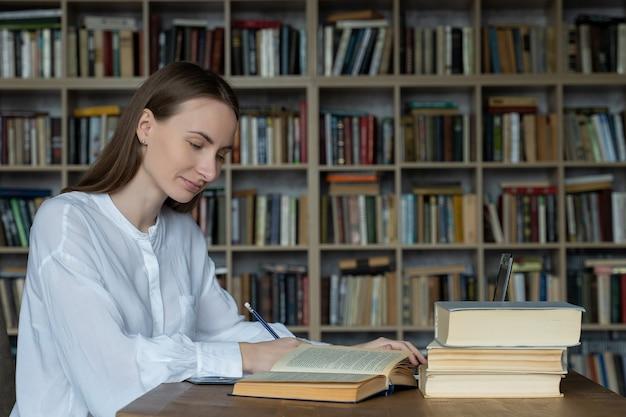 Młoda kobieta siedzi przy stole z książkami i laptopem w bibliotece uniwersyteckiej i studia