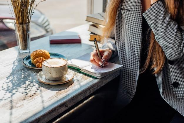 Młoda kobieta siedzi przy stoliku przy oknie i pisze w zeszycie.