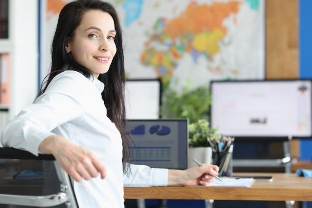 Młoda kobieta siedzi przy swoim stole roboczym w biurze