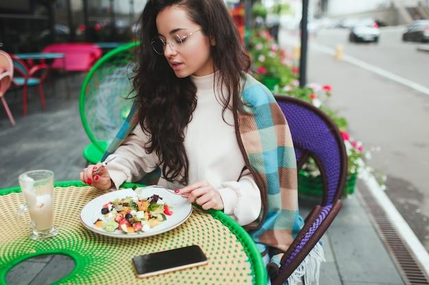 Młoda kobieta siedzi sama w kawiarni lub restauracji