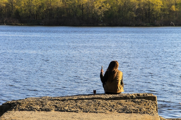 Młoda kobieta siedzi samotnie na molo z filiżanką kawy. widok z tyłu