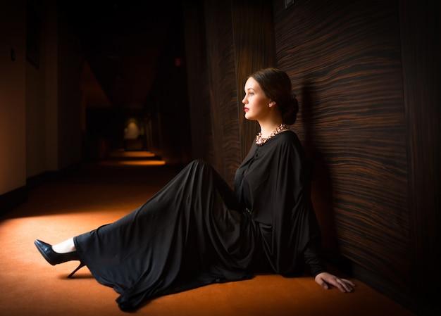 Młoda kobieta siedzi samotnie na ziemi