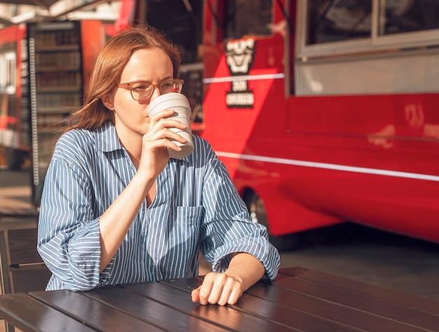 Młoda kobieta siedzi samotnie ze składaną filiżanką kawy ekologicznej w pobliżu ulicznej ciężarówki z jedzeniem nowoczesny miejski styl życia