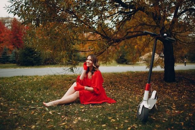 Młoda kobieta siedzi skuterem elektrycznym w czerwonej sukience w parku miejskim jesienią
