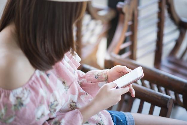Młoda kobieta siedzi telefon komórkowego i używa