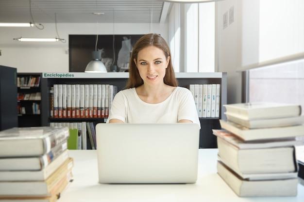 Młoda kobieta siedzi w bibliotece z laptopem